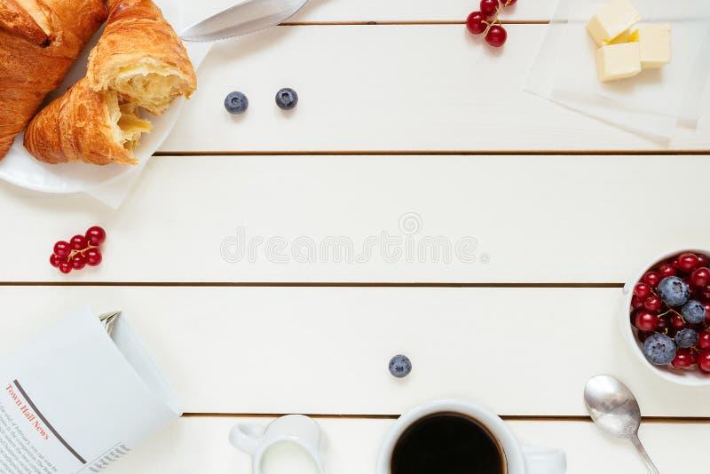 Desayuno sabroso con el café, bayas, cruasán en la tabla de madera blanca con el espacio de la copia, visión superior fotos de archivo libres de regalías