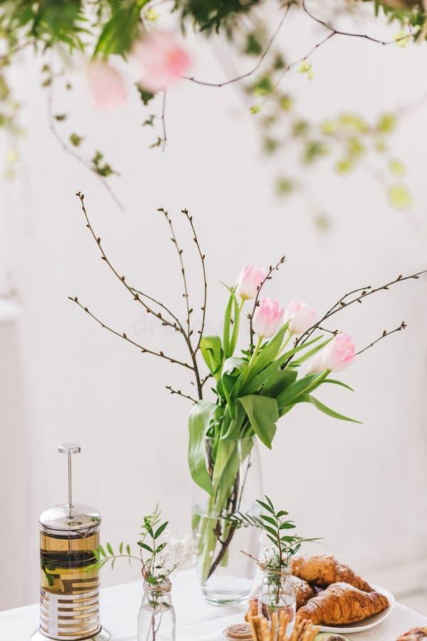 Desayuno sabroso con los cruasanes, empanada, té en la tabla Ramo de tulipanes imagen de archivo libre de regalías