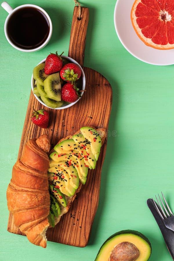 Desayuno sabroso - cruasán con el aguacate, la fruta y el café imagen de archivo