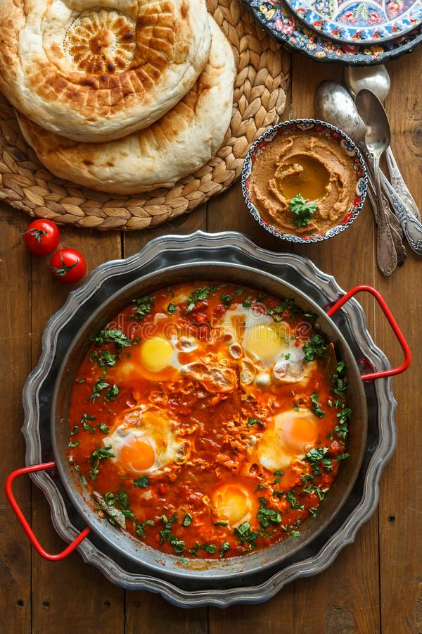 Desayuno sabroso Shakshuka en una cacerola del hierro Huevos fritos con los tomates, comida sana imagenes de archivo