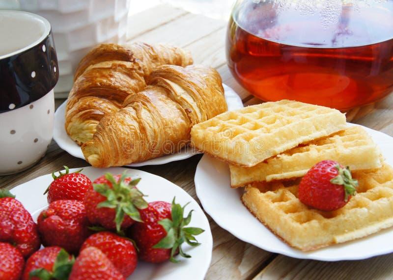 Desayuno sabroso - té, croissants, obleas fotos de archivo