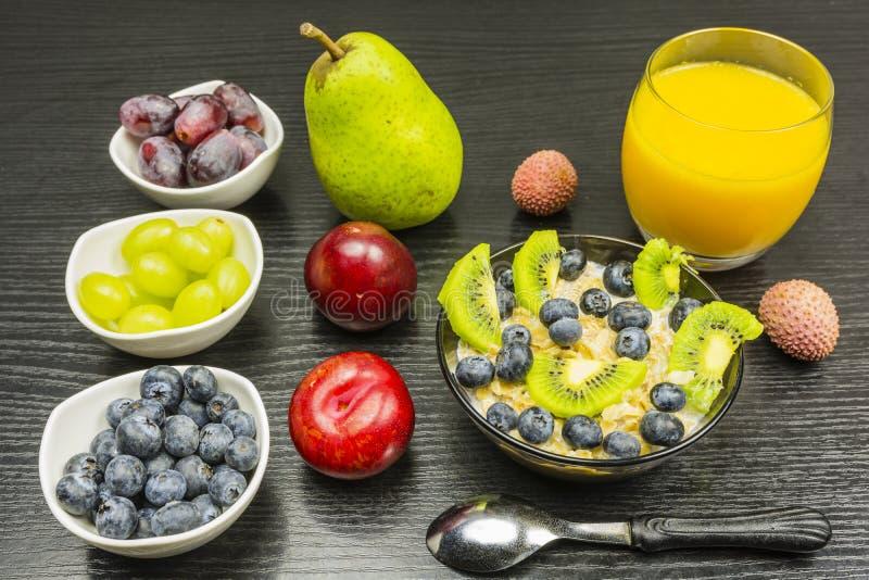 Desayuno sabroso y sano - gachas de avena con leche, fruta y Orán imagenes de archivo
