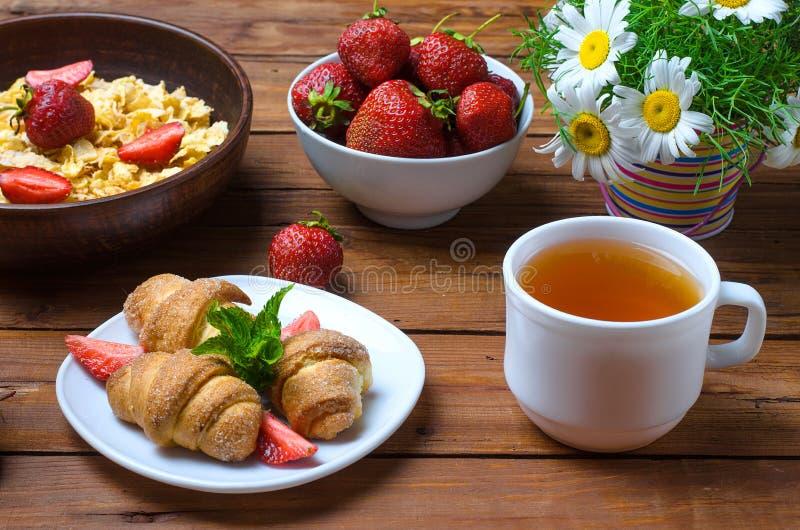Desayuno sano: avenas, fresas, té y cruasán imagen de archivo libre de regalías