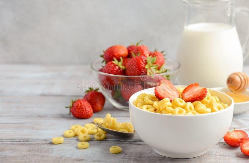 Desayuno sano - cereal en un cuenco blanco con las fresas, la leche y la miel imagen de archivo