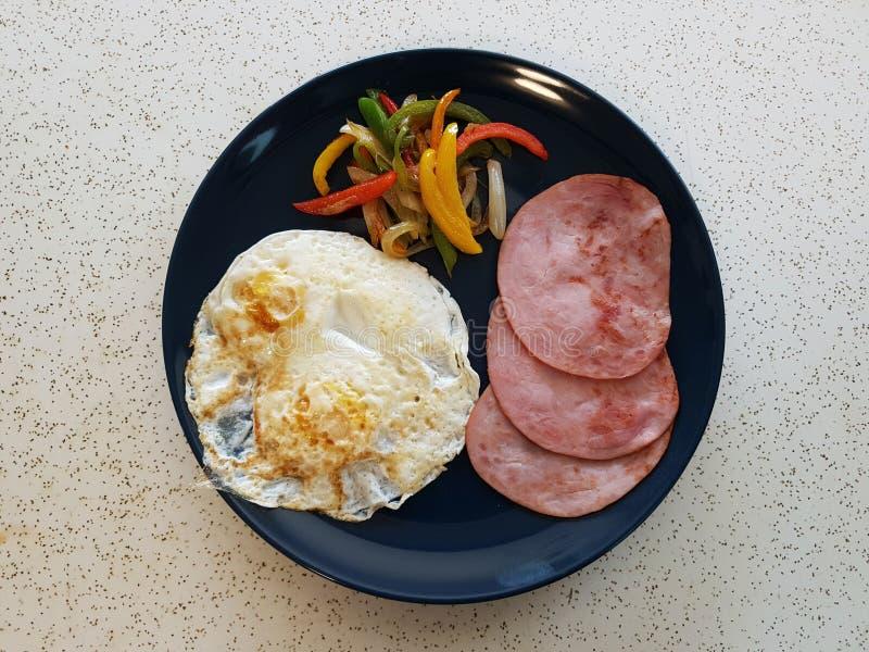 Desayuno sano con bacon de lomo, el huevo frito sobre-fácil, y pimientas imagen de archivo libre de regalías