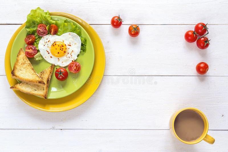 Desayuno sano con el huevo frito en forma de corazón, tostada, cereza tom fotos de archivo