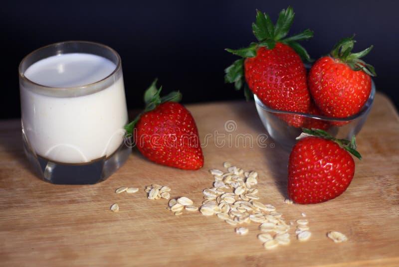 Desayuno sano con la fresa, los cereales, la avena y el vidrio de leche fotos de archivo libres de regalías