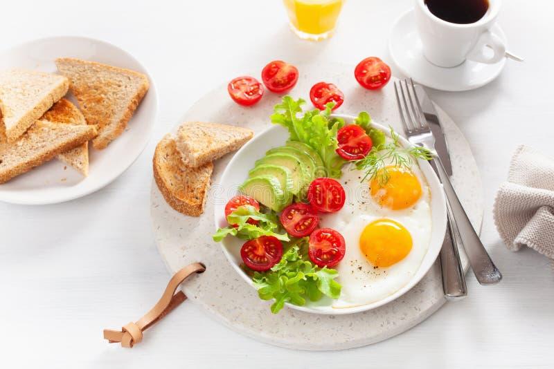 Desayuno sano con los huevos fritos, el aguacate, el tomate, las tostadas y el café imágenes de archivo libres de regalías