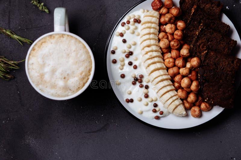 Desayuno sano con pan delicioso, el plátano, la avellana, el yogur en cuenco y una taza de café, de latte o de cacao con leche en fotografía de archivo