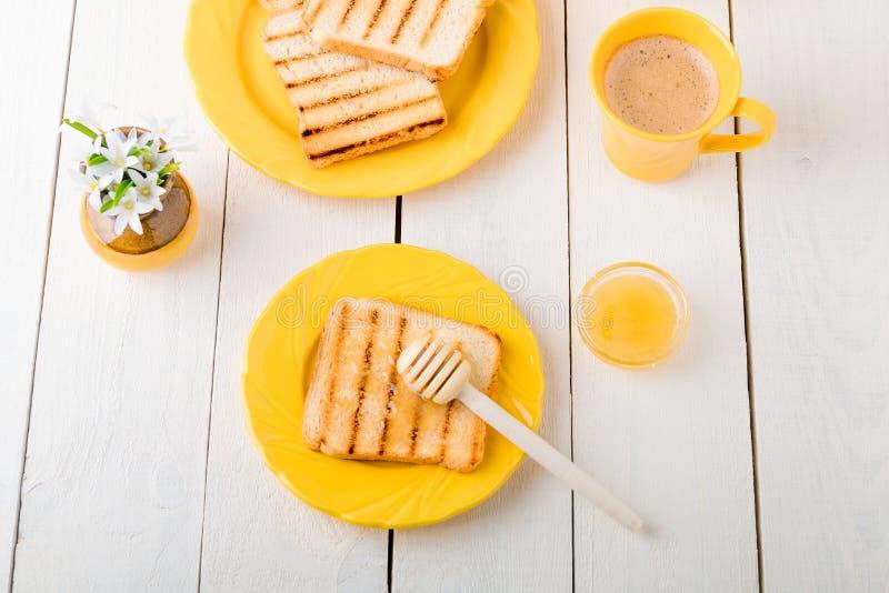 Desayuno sano con pan y miel tostados cerca del florero con las flores en el fondo blanco Tono amarillo Visión superior imagenes de archivo