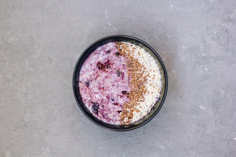 Desayuno sano de la mañana con el atasco del arándano - gachas de avena del trigo con las bayas y las semillas de lino en fondo c fotos de archivo