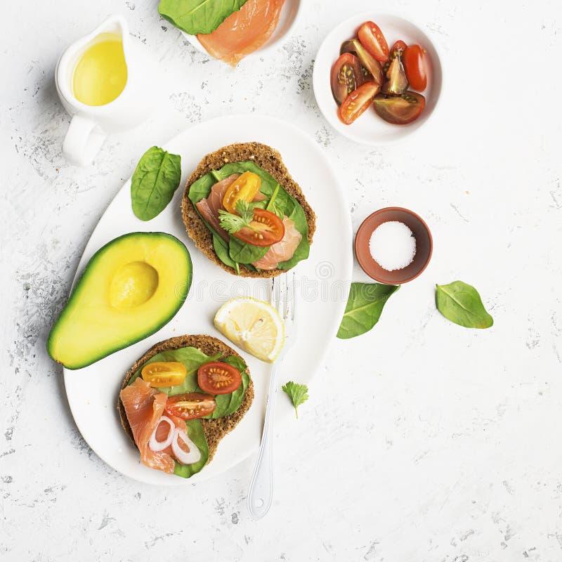 Desayuno sano: el cereal rueda con los salmones, tomates de cereza, espinaca, aguacate arándano en un fondo ligero tapa fotografía de archivo libre de regalías
