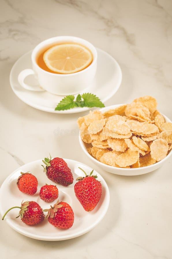 desayuno sano en un fondo/un desayuno blancos con la fresa, las escamas, la miel y el té en un fondo de mármol blanco fotos de archivo libres de regalías