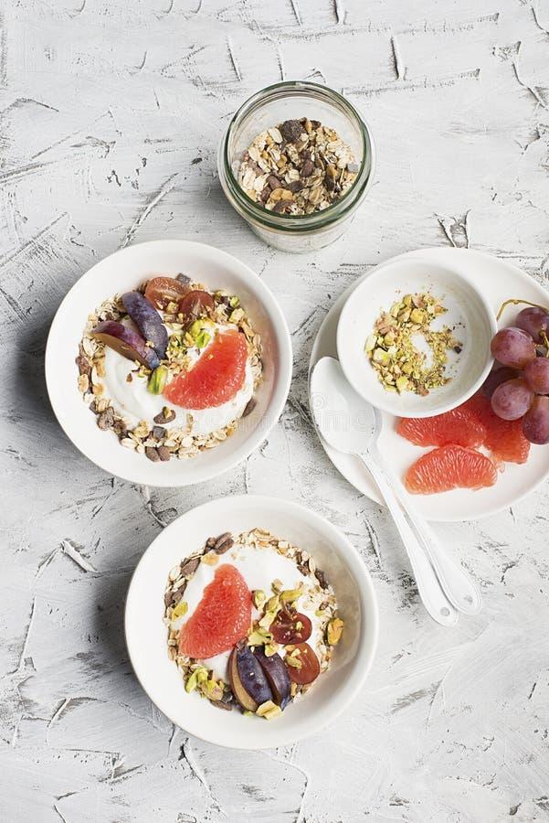 Desayuno sano estacional: yogur, granola del chocolate, pomelo rosado, uvas, pistachos Visión superior Copie el espacio plano imagen de archivo