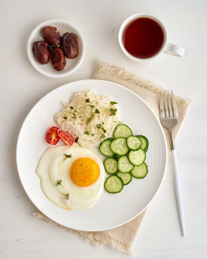 Desayuno sano - huevo frito con los tomates y el pepino de cereza en el fondo blanco ligero, dieta de la rociada del fodmap, glut foto de archivo libre de regalías