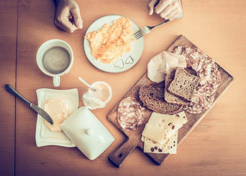 Desayuno sano, huevos revueltos, café sólo, bocadillos con queso del salami, en una tabla de madera, visión superior foto de archivo