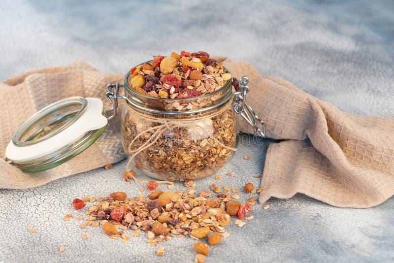 Desayuno sano - los tarros de cristal de la avena forman escamas, granola con secado fotografía de archivo