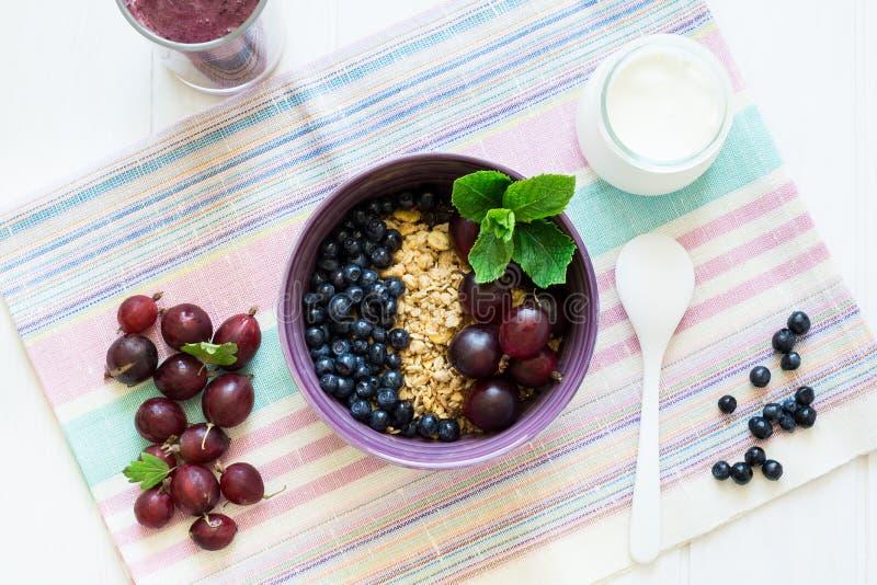 Desayuno sano: muesli con la grosella espinosa y zarzamora, yogur, smoothie del arándano y molletes del chocolate imagen de archivo libre de regalías