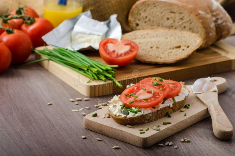 Desayuno sano - pan hecho en casa de la cerveza con el queso, tomates fotos de archivo
