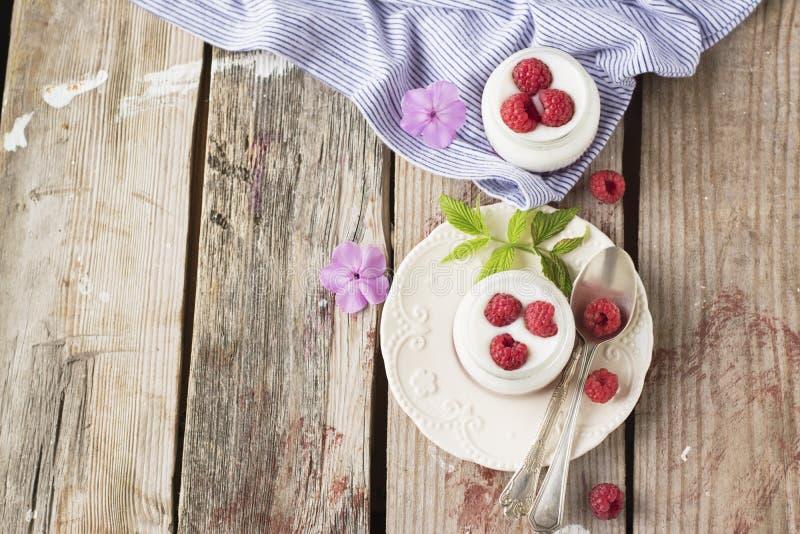 Desayuno sano para el lote fresco dos de yogur con las frambuesas maduras jugosas imagenes de archivo