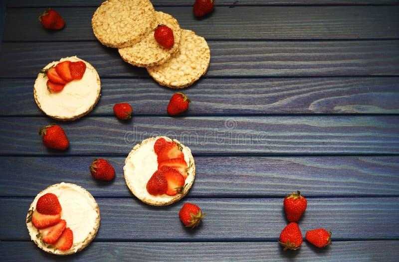 Desayuno sano y un bocado del pan del arroz con las fresas rojas, con queso en un fondo de madera azul fotos de archivo libres de regalías