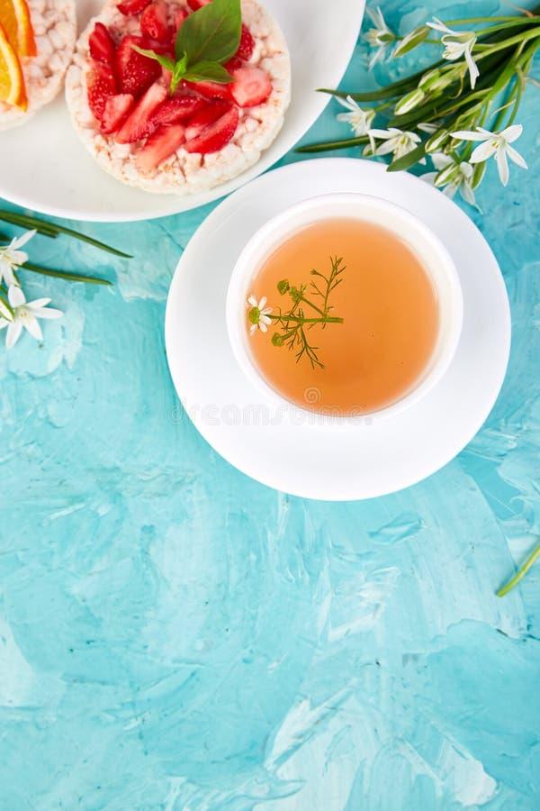 Desayuno - té, biscote curruscante del arroz con las frutas frescas en fondo azul fotografía de archivo