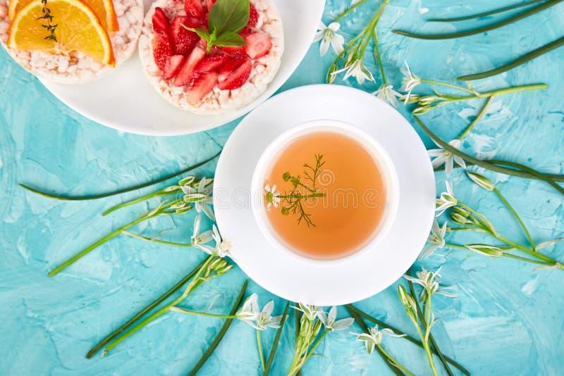 Desayuno - té, biscote curruscante del arroz con las frutas frescas en fondo azul foto de archivo