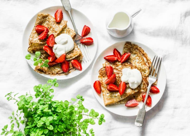 Desayuno, tabla del postre - crespones con las fresas y crema en un fondo blanco, visión superior imagenes de archivo