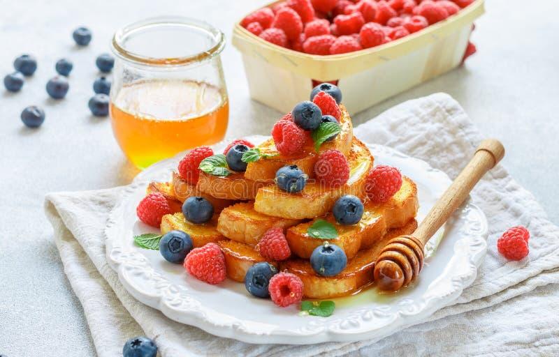 Desayuno tradicional - tostada francesa con la miel y las bayas frescas - frambuesas y arándanos fotografía de archivo