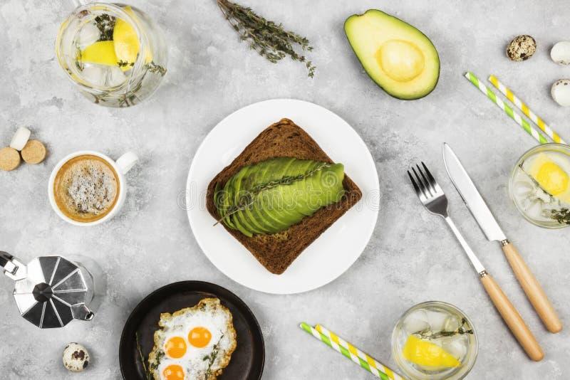 Desayuno tradicional - tueste del pan de centeno con el aguacate, huevos fritos de los huevos de codornices, limonada en un fondo fotos de archivo