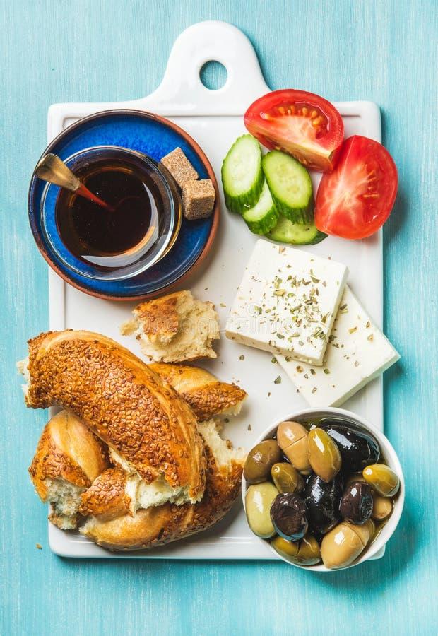 Desayuno tradicional turco con el queso feta, las verduras, las aceitunas, el panecillo del simit y el té fotografía de archivo