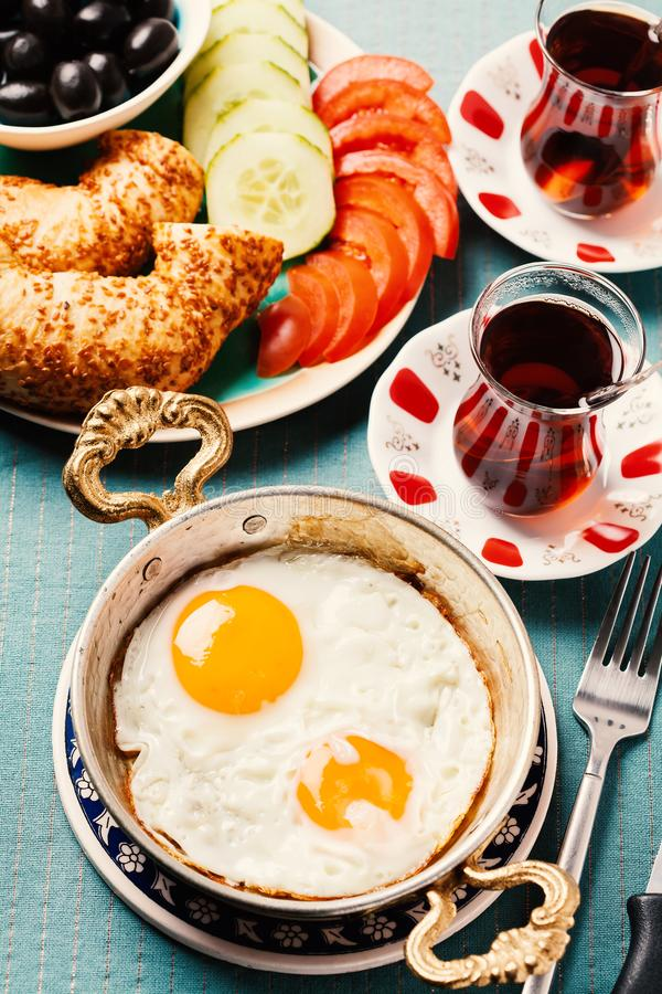 Desayuno turco tradicional con los huevos fritos y el té fotos de archivo