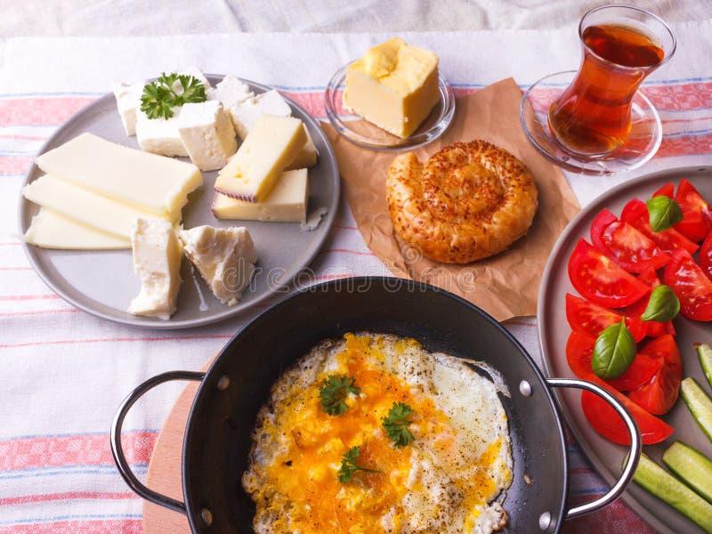 Desayuno turco tradicional - huevos fritos, verduras frescas, aceitunas, queso, torta y t? imagen de archivo