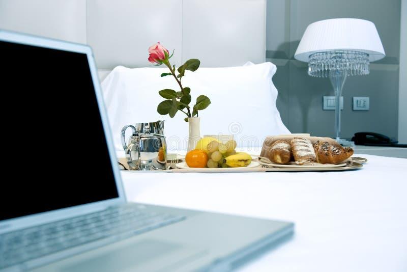 Desayuno y computadora portátil del hotel foto de archivo