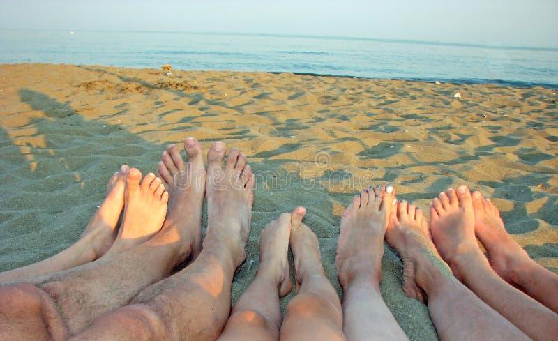 Descalzo de una familia en la orilla del mar en la playa con c foto de archivo