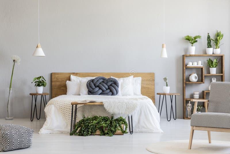 Descanso azul do nó na cama de madeira branca em wi interiores do quarto cinzento fotos de stock
