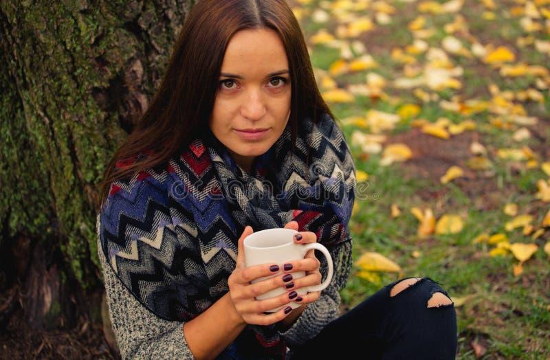 Descanso bonito da menina e café bebendo que sentam-se no jardim do outono imagem de stock royalty free