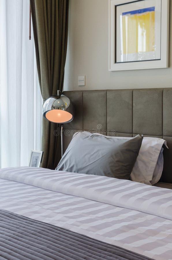 Descanso cinzento na cama com lâmpada moderna fotos de stock royalty free