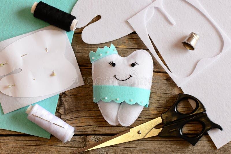 Descanso da fada de dente de feltro, molde de papel, folhas de feltro e sucatas, tesouras, linha no fundo de madeira velho Dente  fotografia de stock