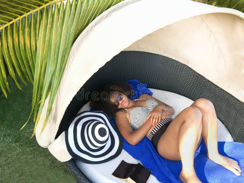 Descanso e abrandamento Salas de estar afro-americanos bonitas da mulher na cabana foto de stock