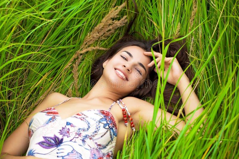 Descanso e dia da jovem mulher que encontram-se para baixo na grama verde imagens de stock royalty free