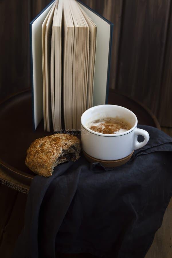 Descanso para tomar café con el cruasán del atasco después de leer foto de archivo libre de regalías