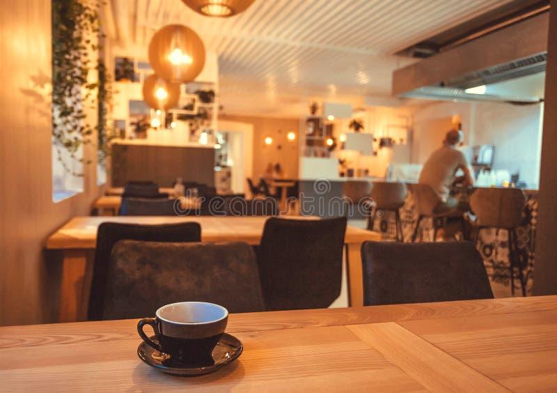 Descanso para tomar café con la taza en la tabla de restaurante o de café Visitante de consumición solo de la barra interior fotografía de archivo libre de regalías