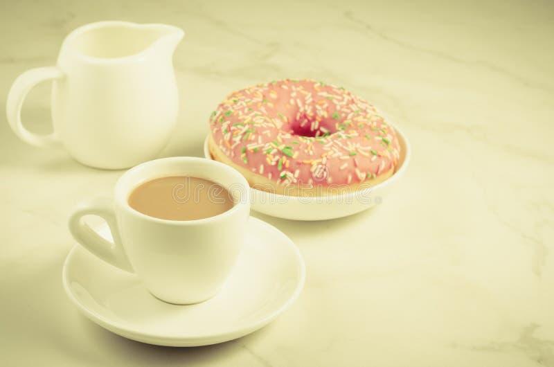 Descanso para tomar café: leche y buñuelo/descanso para tomar café rosados azucarados frescos: leche y buñuelo rosado azucarado f foto de archivo libre de regalías