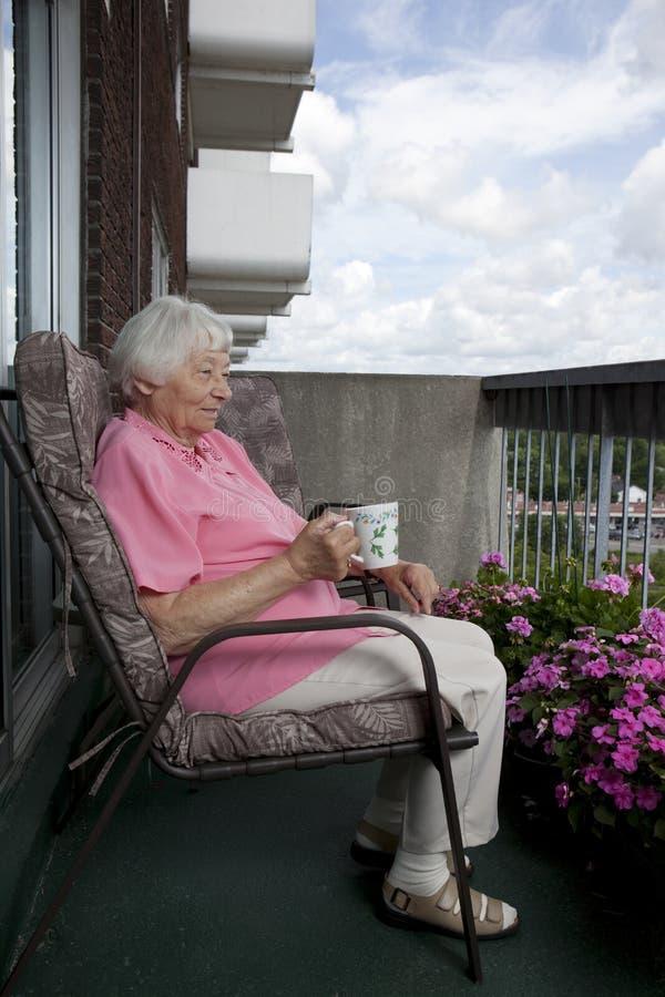Descanso para tomar café mayor de la mujer imagenes de archivo