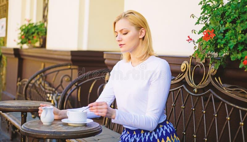 Descanso para tomar café pacífico La cara tranquila elegante de la mujer tiene terraza del café de la bebida al aire libre Café d foto de archivo