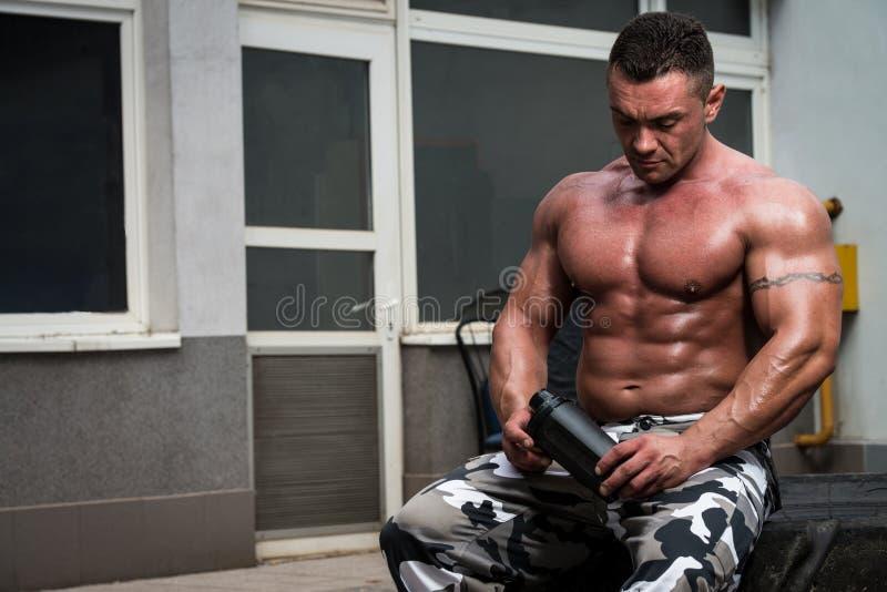 Descanso saudável e água potável do homem após o exercício no gym foto de stock royalty free