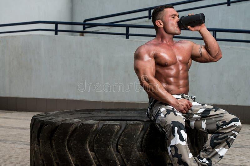 Descanso saudável e água potável do homem após o exercício no gym fotografia de stock