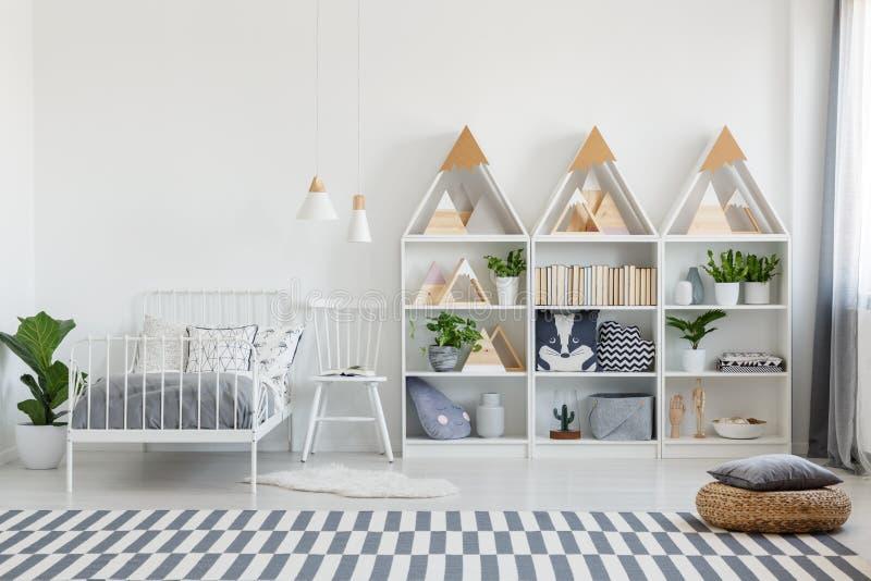 Descansos bonitos e livros em unidades de madeira das prateleiras e uma cadeira por uma cama gêmea em um interior do quarto do ec fotos de stock