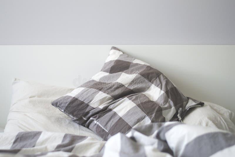 Descansos cinzentos e brancos em uma cama imagem de stock